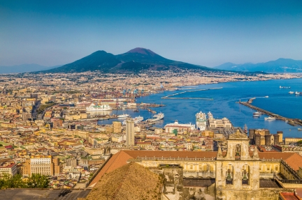 Scenic picture-postcard view of the city of Napoli (Naples) with famous Mount Vesuvius in the background in golden evening light at sunset, Campania, Italy